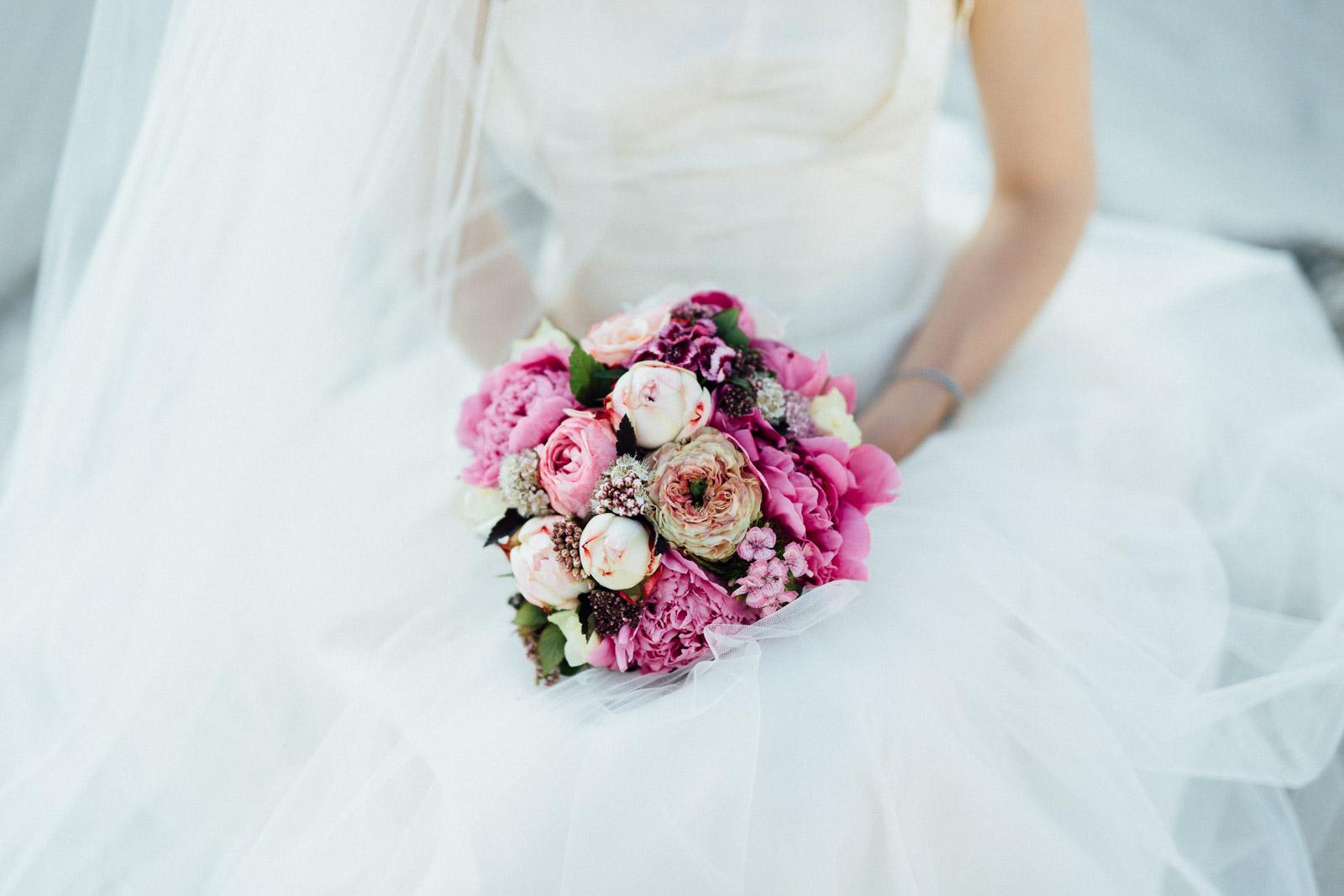 Braut im Brautkleid hält einen Brautstrauß auf dem Schoß