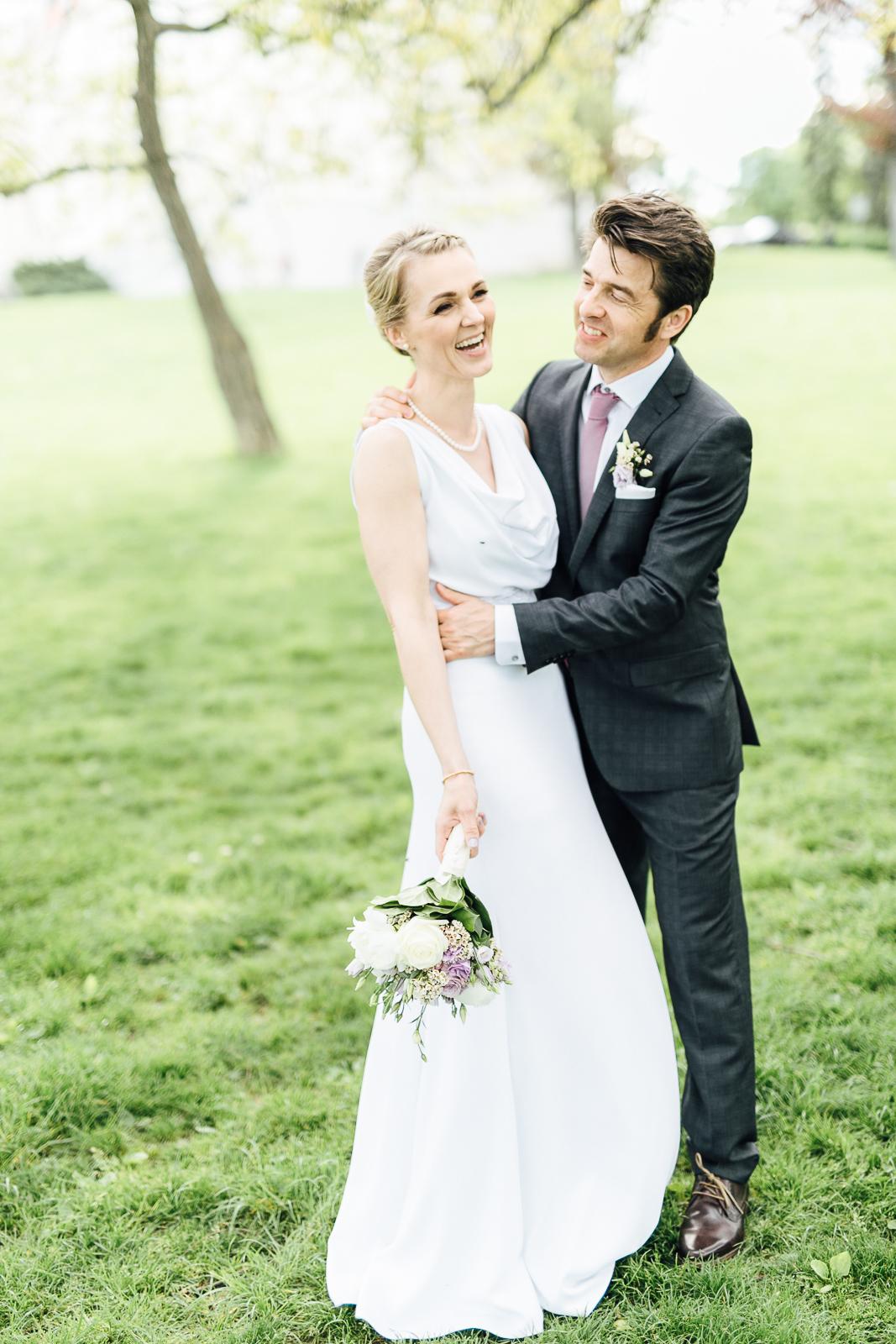 Lachendes Brautpaar auf der Wiese vor Schloss Wilhelminenberg Wien