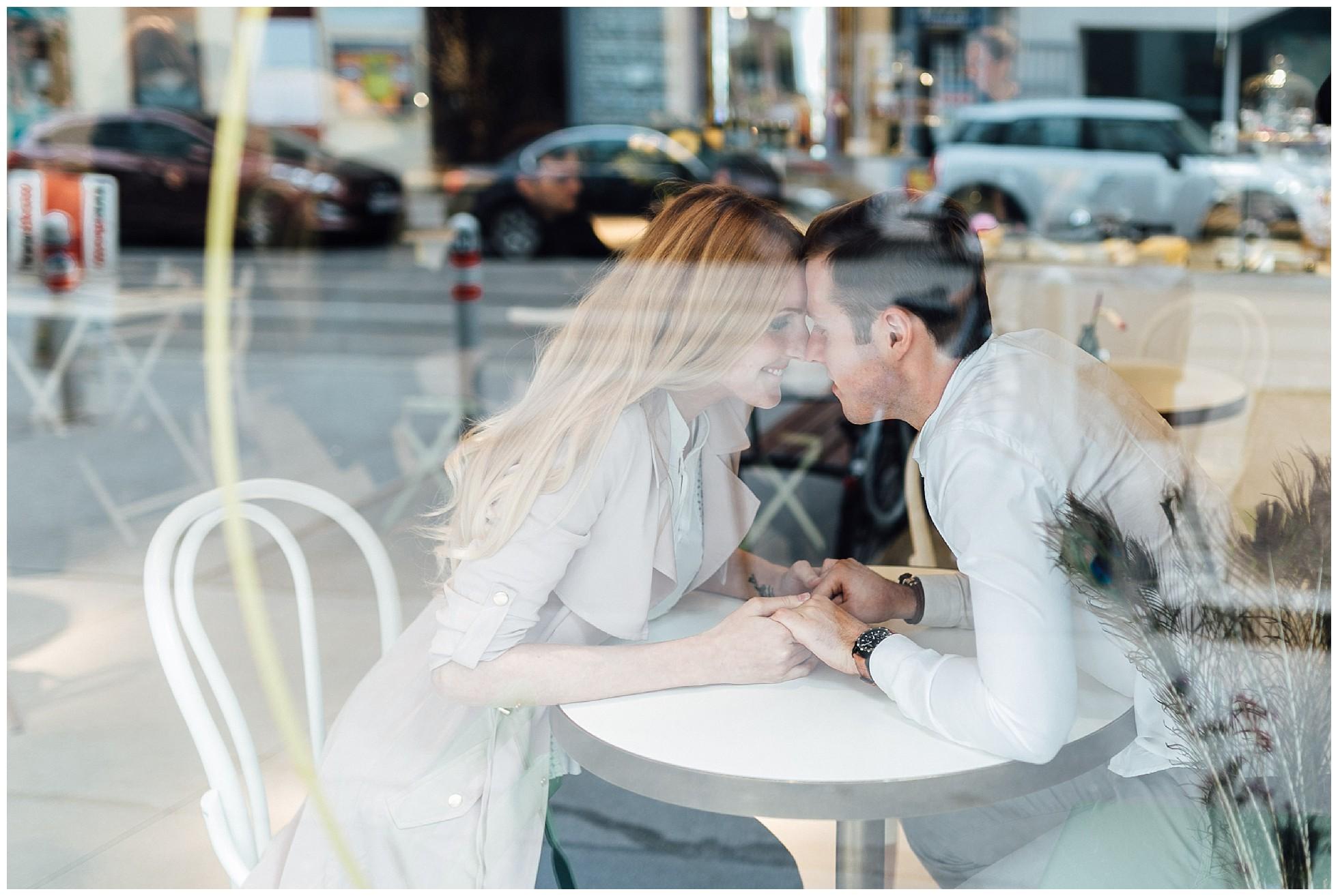 Verliebtes Paar durch die Scheibe eines Cafés fotografiert