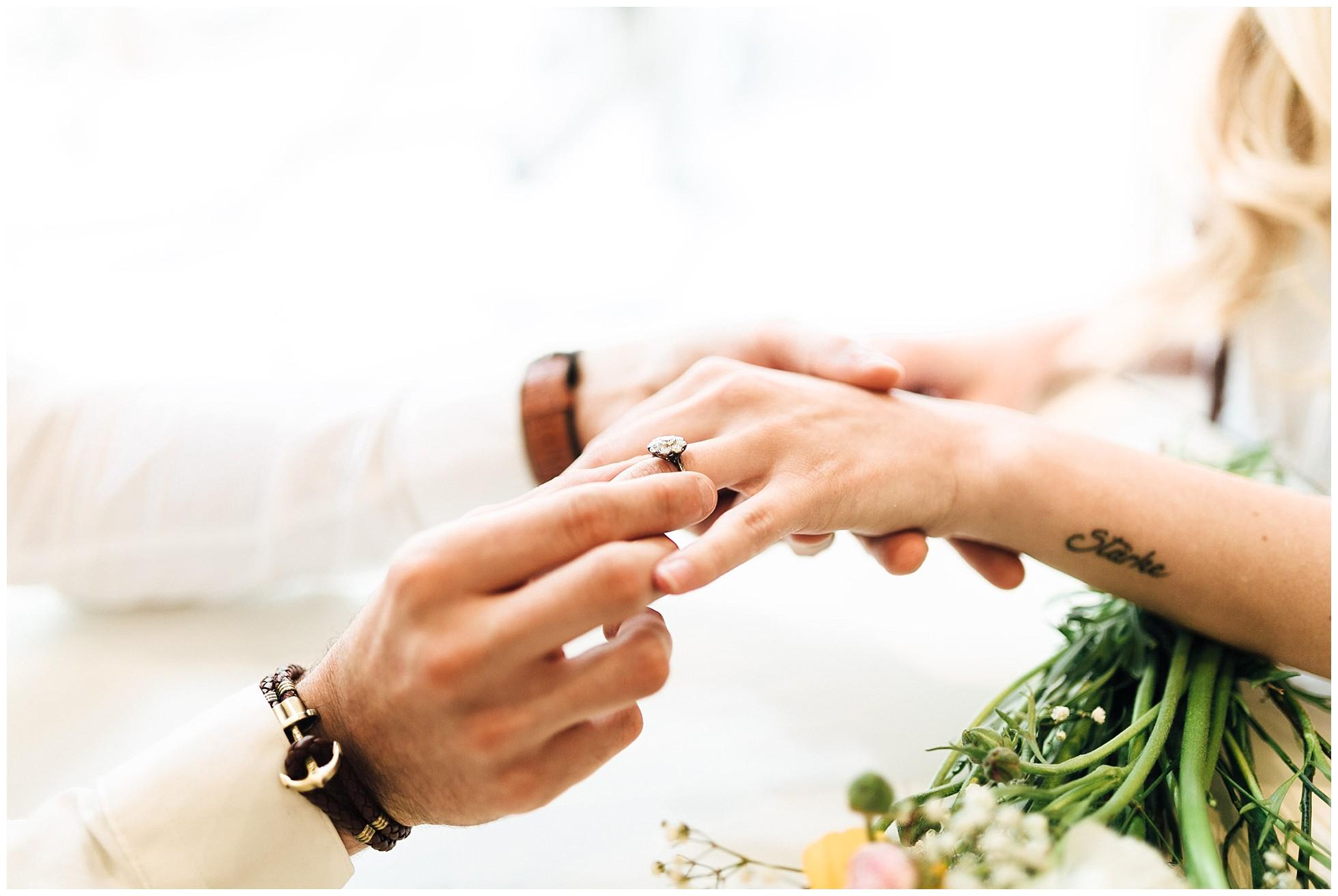 Ein Mann steckt einen Ring an den Finger einer Frau beim Verlobungsshooting in Wien