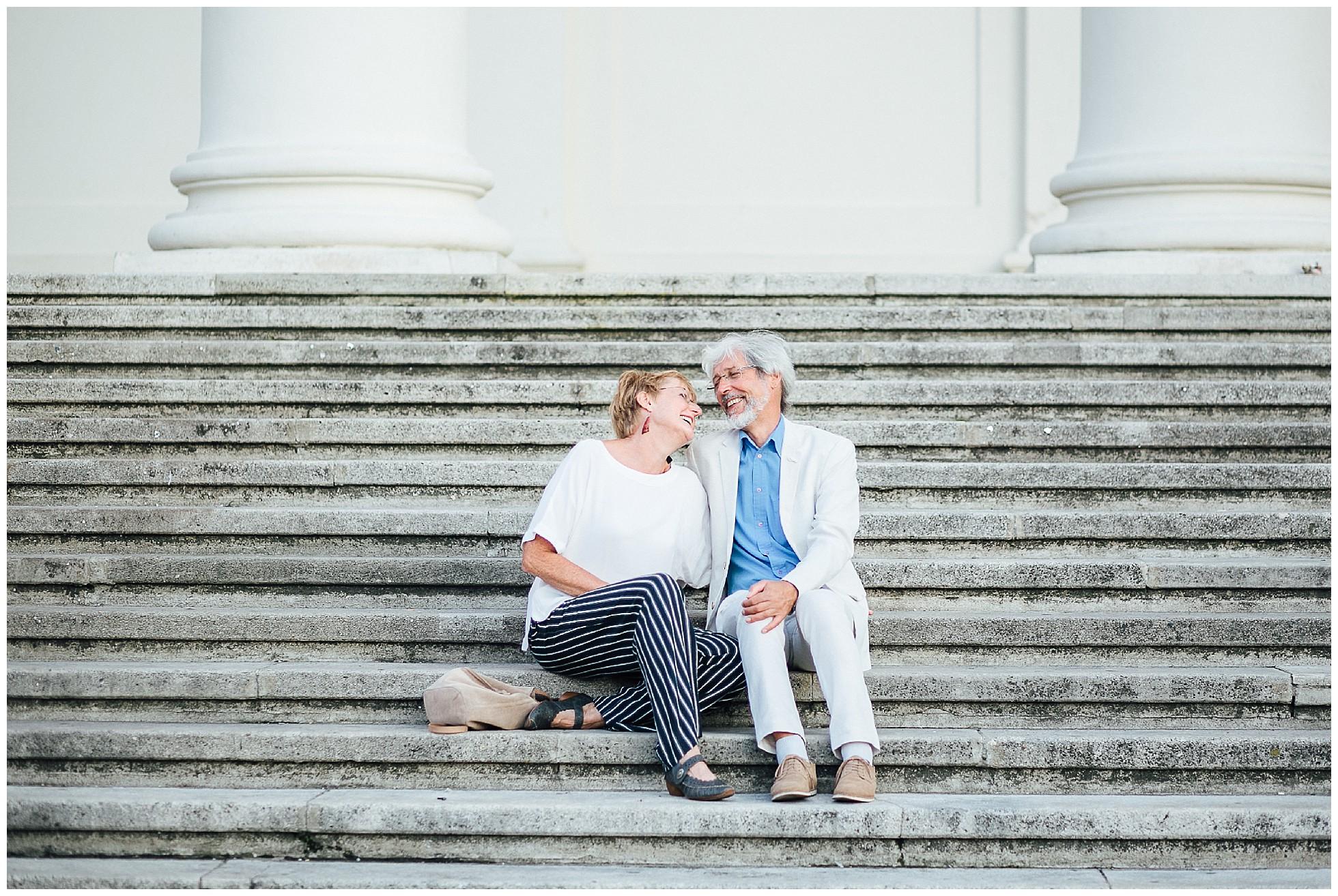 Ein älteres Paar auf den Stufen der Karlskirche in Wien
