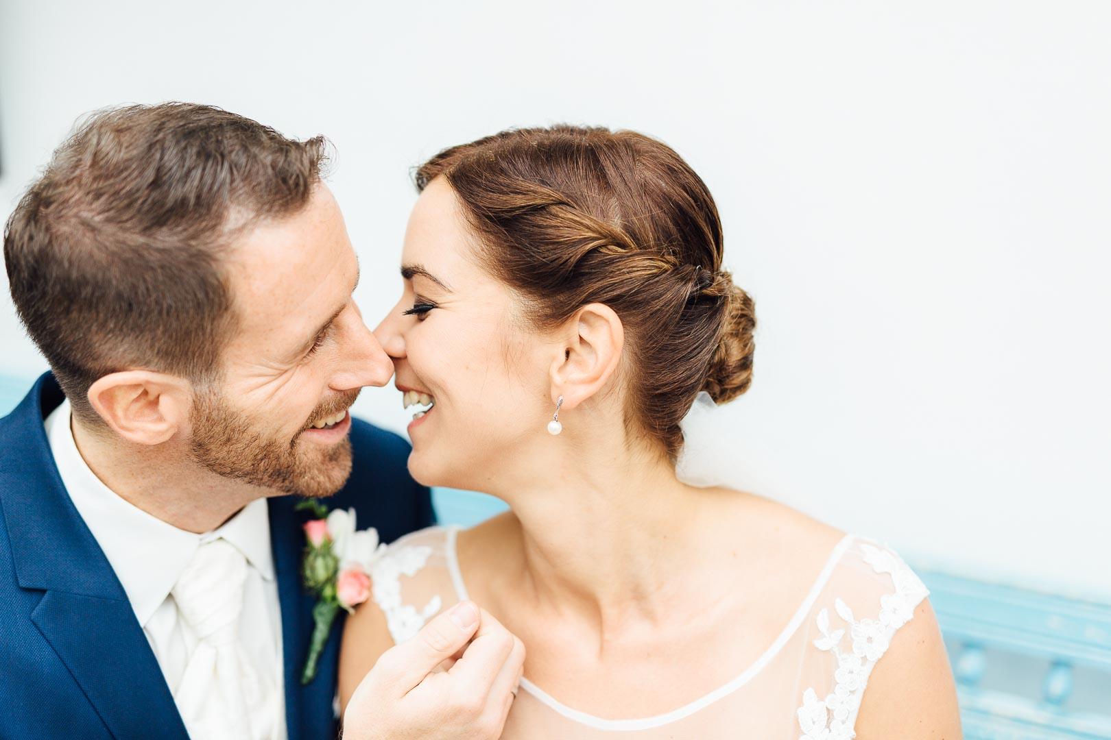 Ein lachendes Brautpaar, das sich zugewandt sitzt
