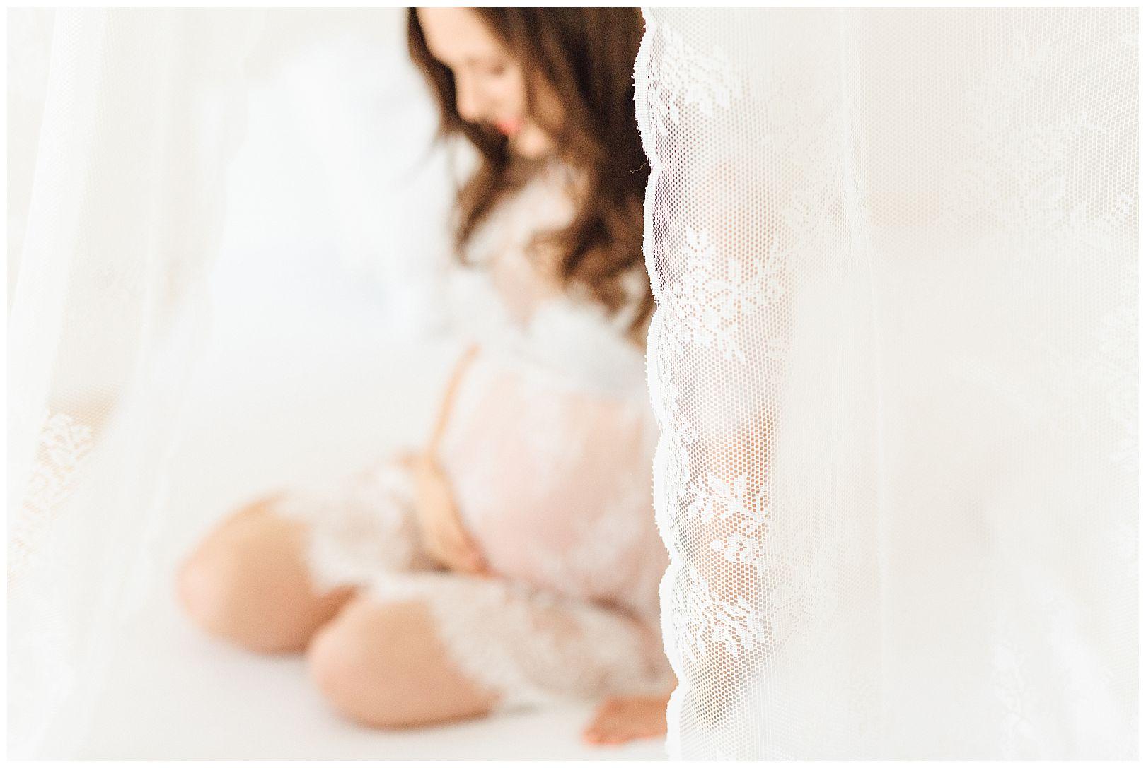Boudoirfoto einer schwangeren Frau im Spitzenkleid