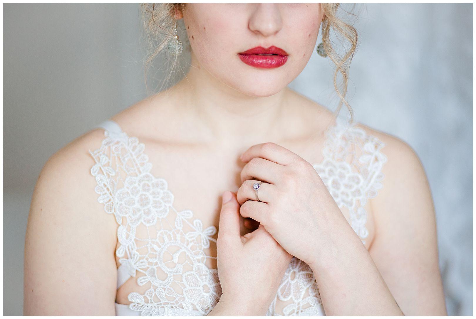 Sinnliches Teilportrait einer Frau mit roten Lippen und vor der Brust gehaltenen Händen