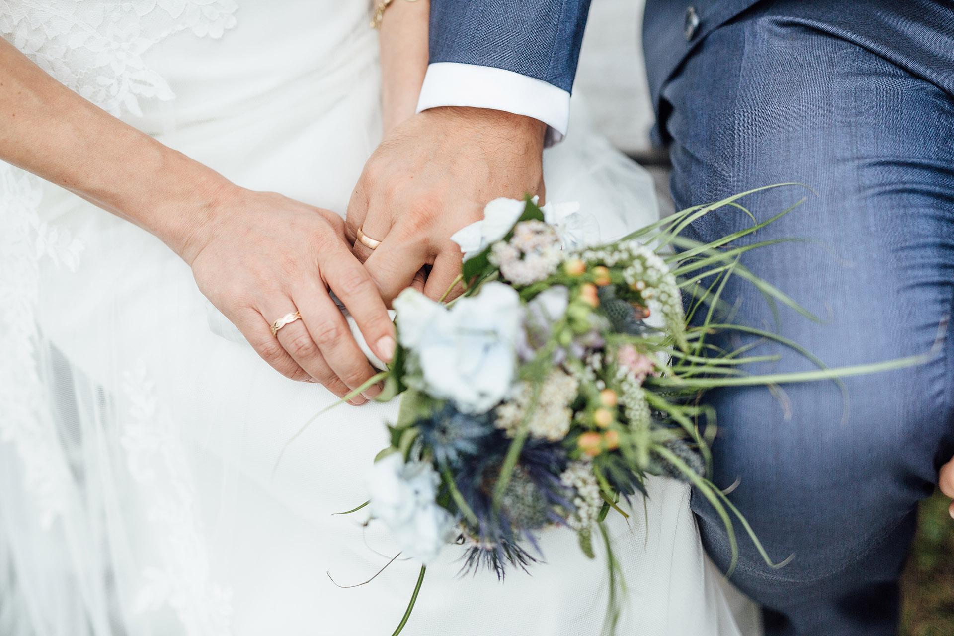 Hände eines Brautpaares halten den Brautstrauß bei der Trauung im Standesamt Wien