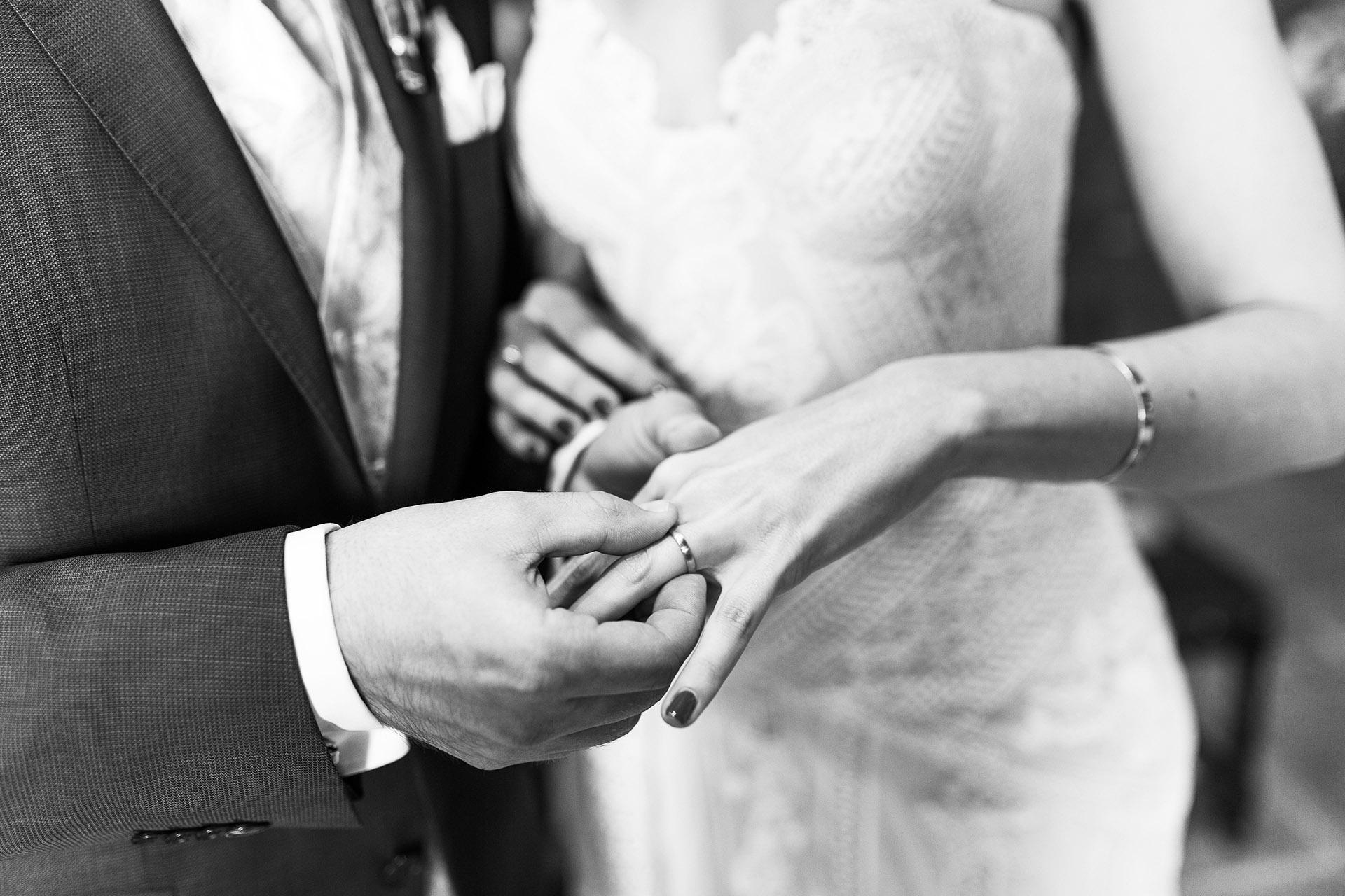 Eine männliche Hand steckt einer Frauenhand einen Ring an den Finger bei einer standesamtlichen Trauung in Wien