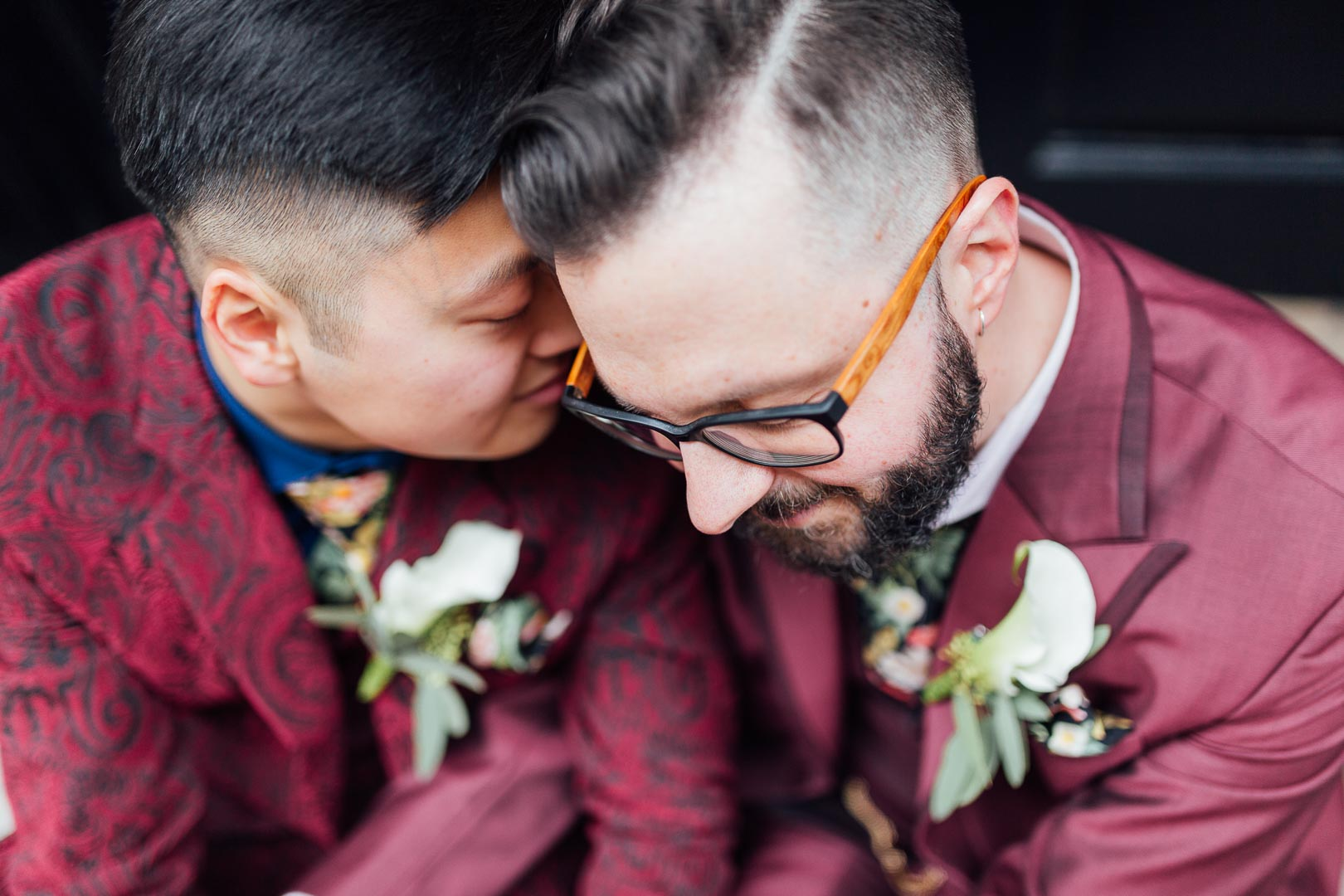 Zwei Bräutigame in weinroten Anzügen lehnen ihre Köpfe romantisch aneinander
