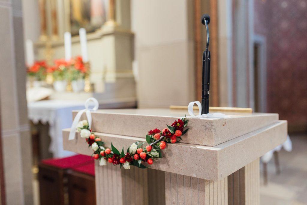 Blumendeko an einem Rednerpult in einer Kirche