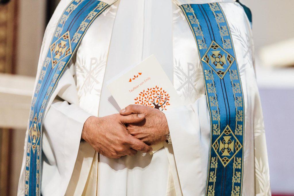 Hände und Umhang eines Pfarrers eine Karte haltend