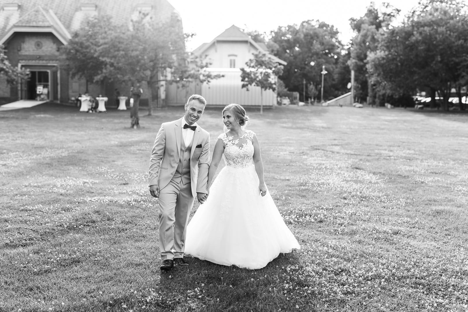 Lachendes Brautpaar geht Hand in Hand über eine Wiese