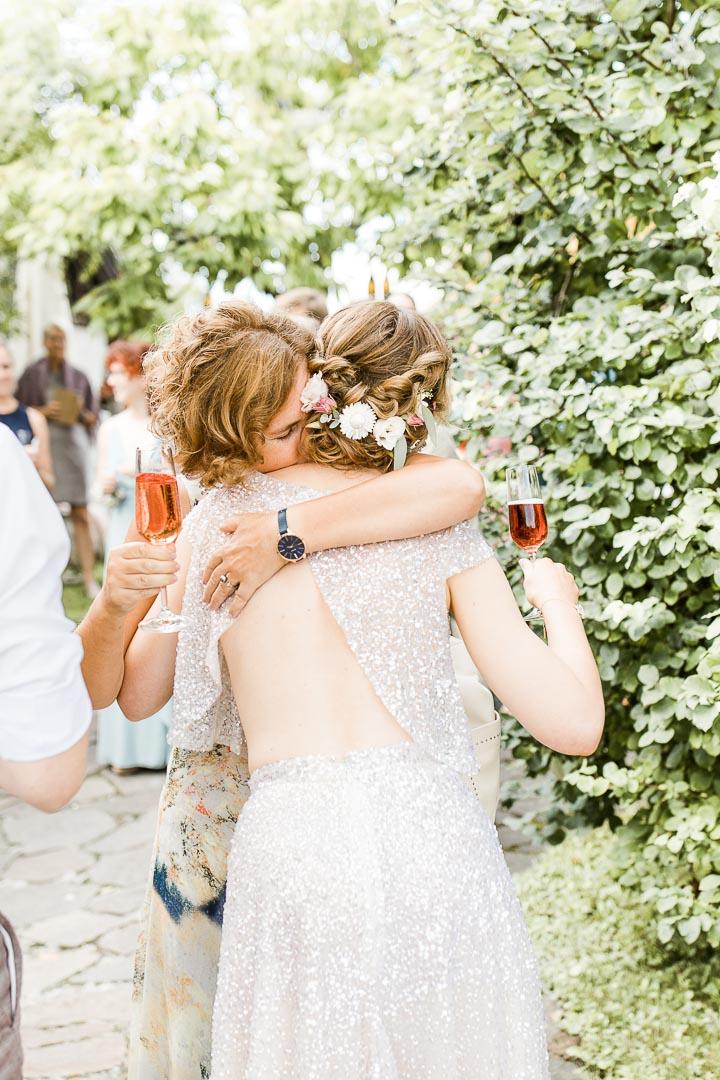 Eine Frau umarmt eine Frau in elegantem Brautkleid emotional