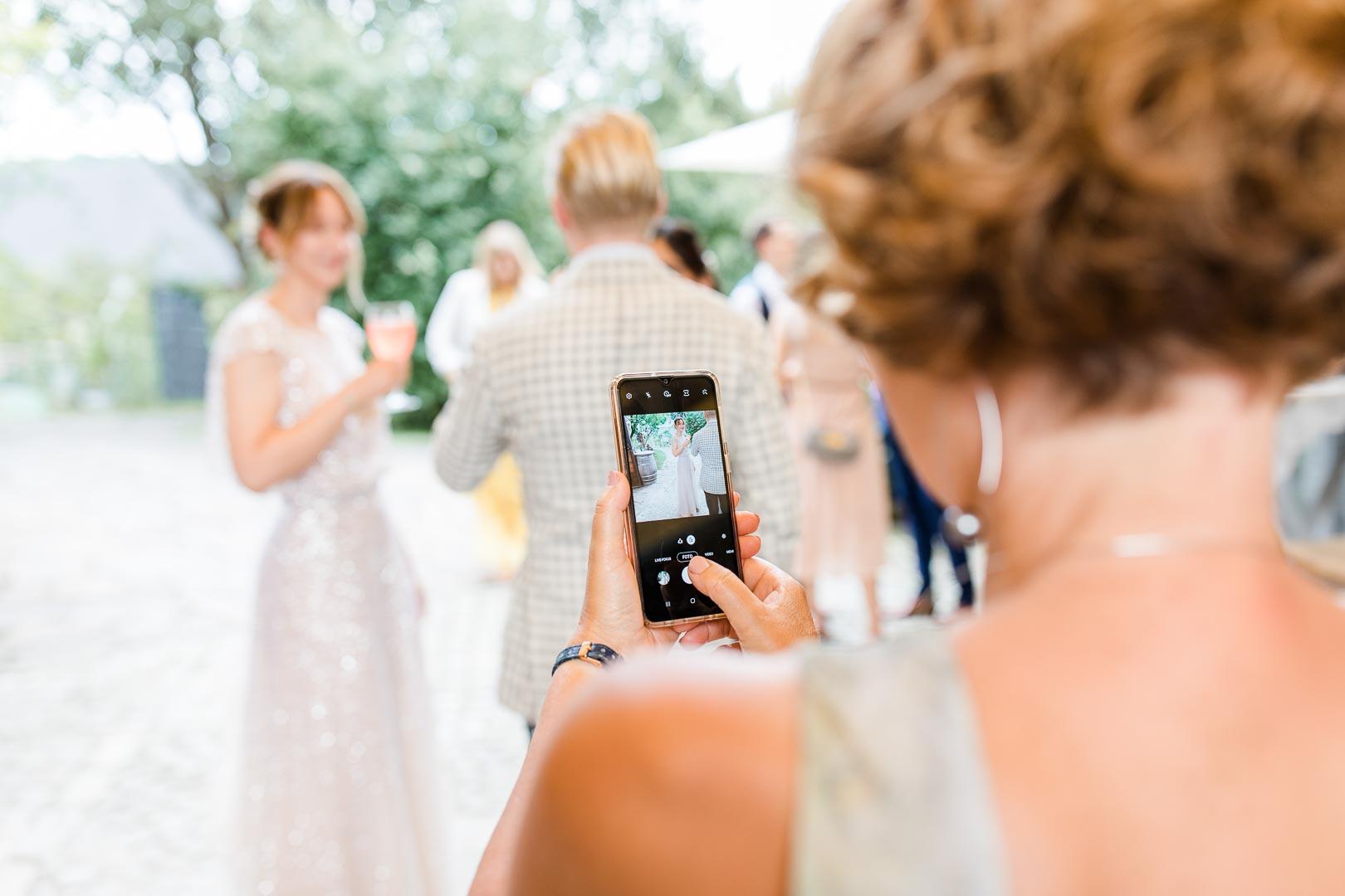 Rückenansicht einer Frau, die mit dem Handy eine Braut fotografiert