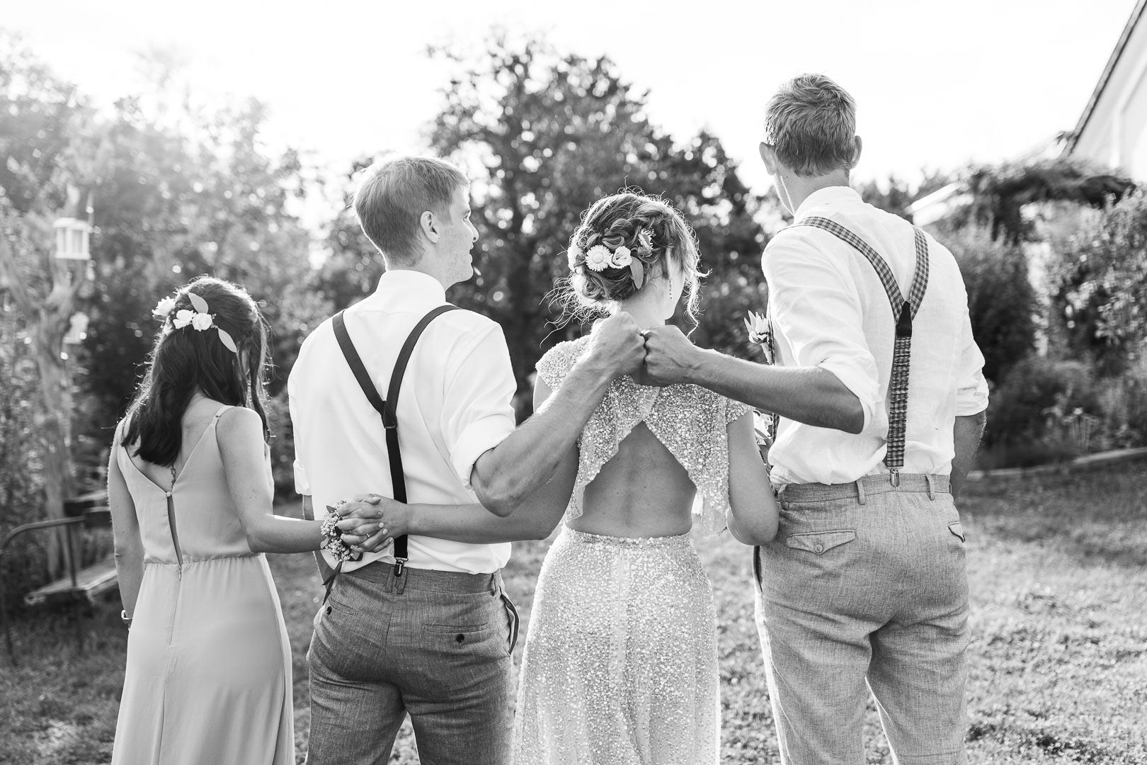 Rückenansicht von einem Brautpaar und Trauzeugen, die sich an den Händen halten