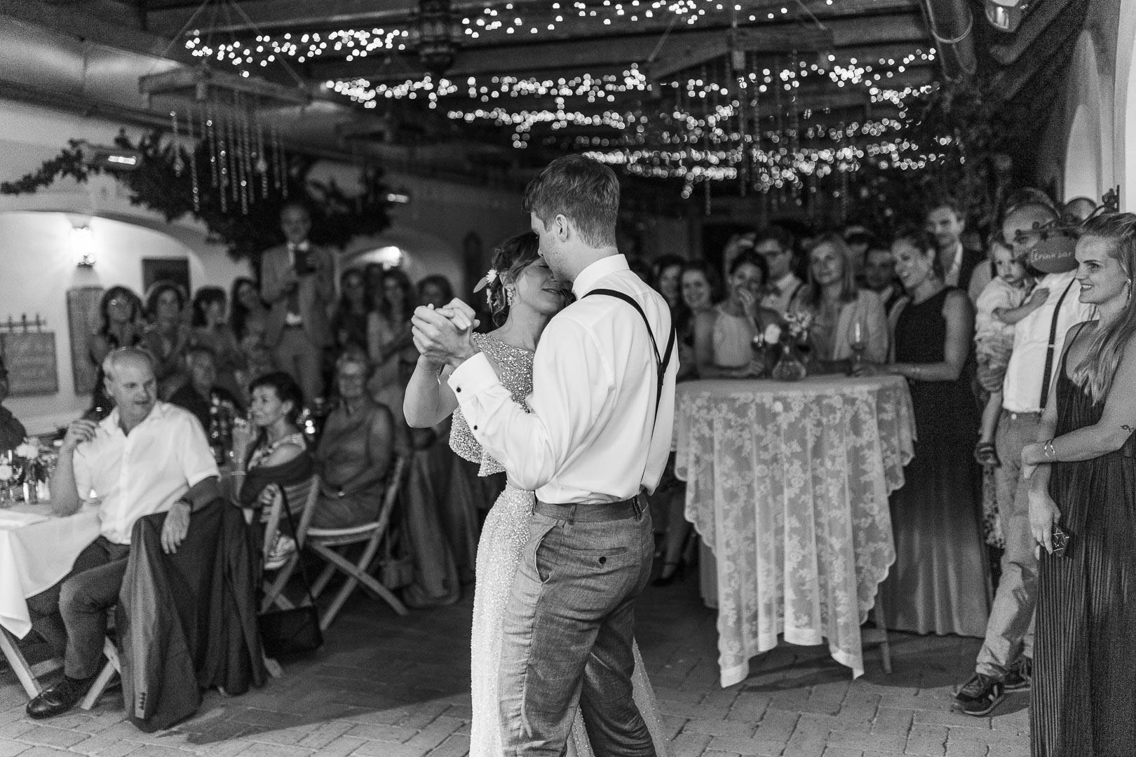 Hochzeitstanz mit Gästen im Hintergrund