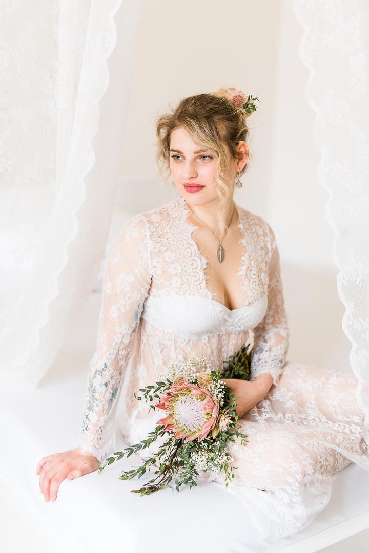Verträumtes Portrait einer Frau im Spitzenkleid mit Blumen