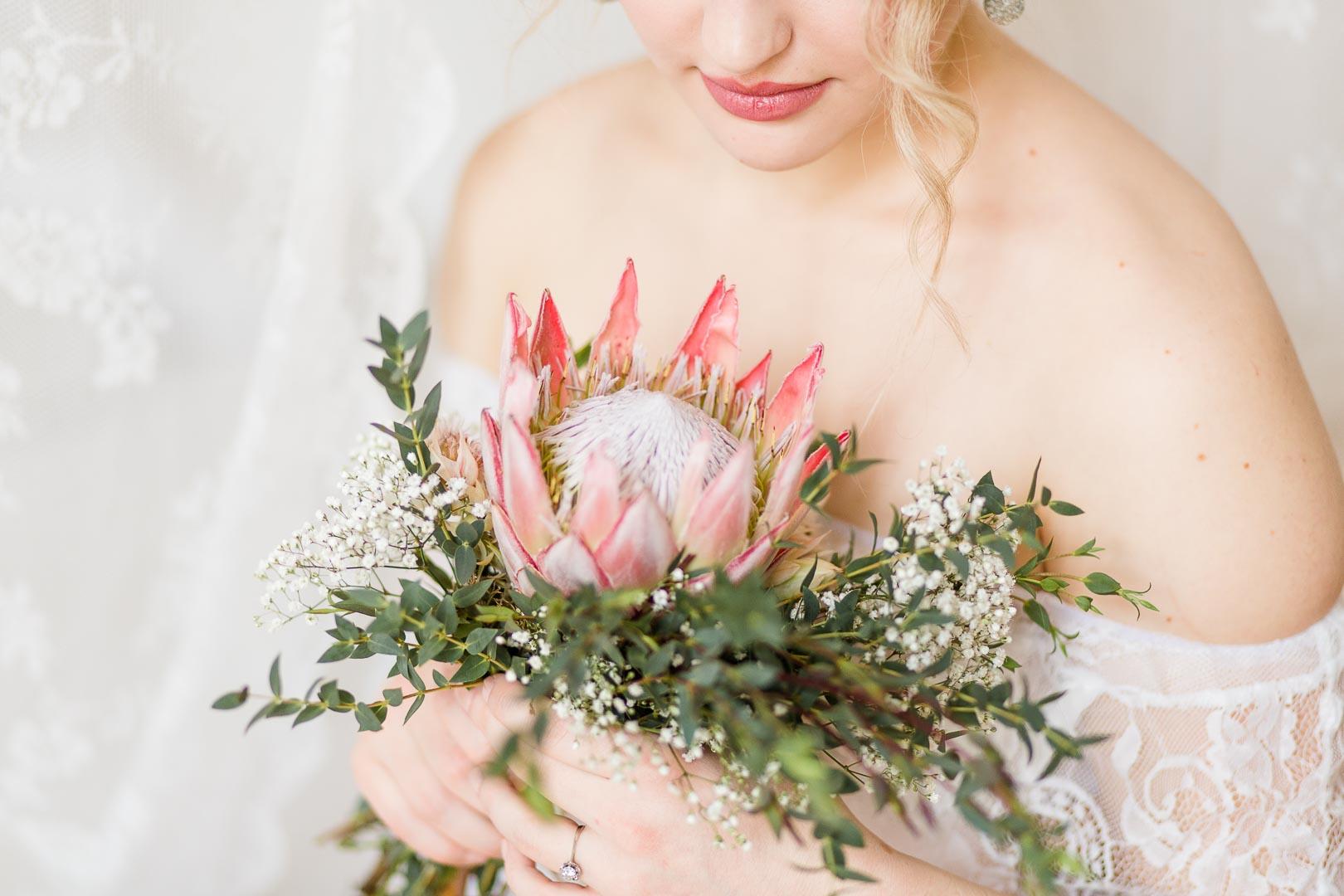 Halbportrait einer Frau mit Spitzenkleid und Protea