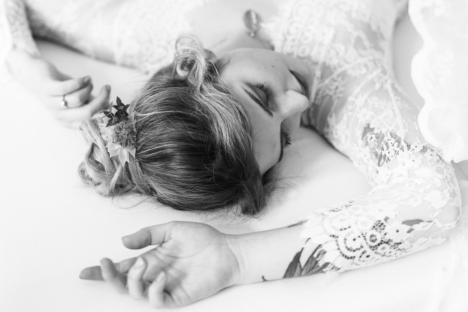 Boudoirsession mit einer tätowierten Frau im Spitzenkleid