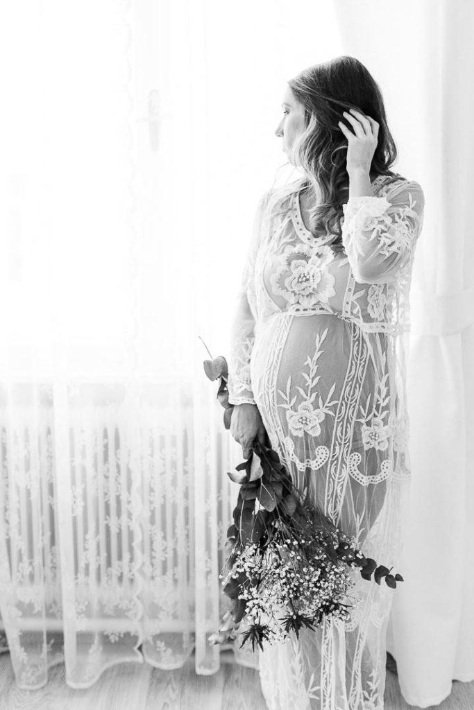 Boudoirfoto einer schwangeren Frau am Fenster